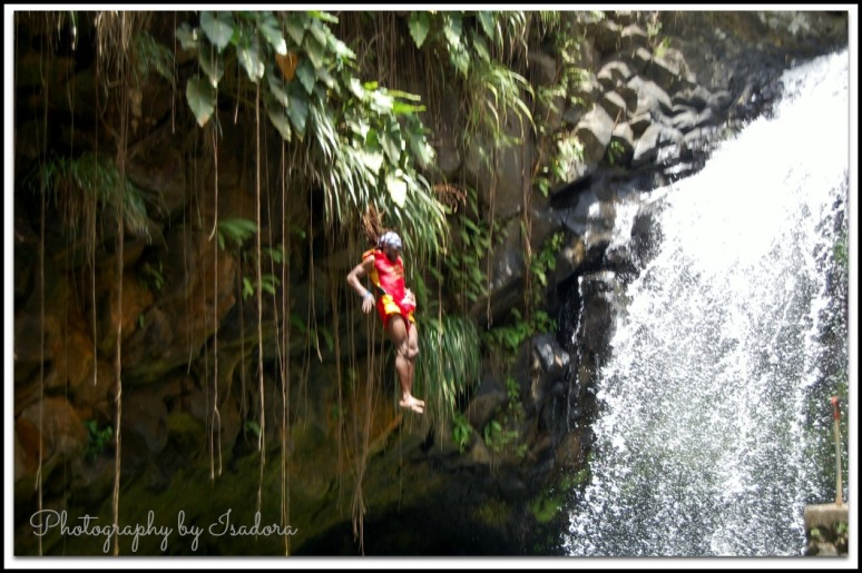 Grenada - Man jumping into Waterfall web